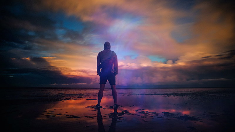photo of man standing on a beach with stormy skies